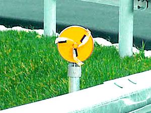 道路の反射板に付いている風車の写真